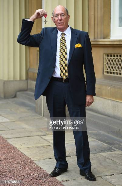 Darts player John Lowe poses with his medal after being appointed Member of the Order of the British Empire at an investiture ceremony at Buckingham...