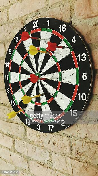 Darts Stuck On Dartboard Mounted On Brick Wall