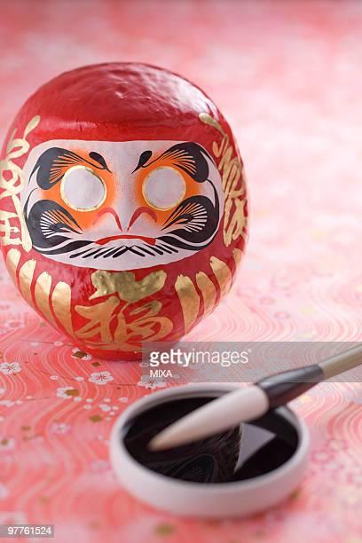 Daruma doll and calligraphy brush