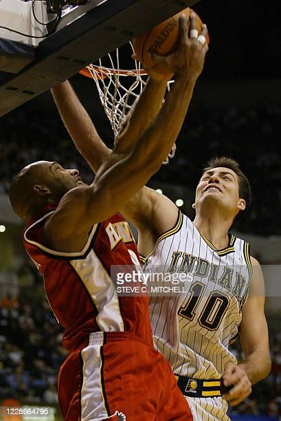 Darvin Hamm of the Atlanta Hawks is fouled by Jeff Foster of the Indiana Pacers in the first half 23 December, 2002 at Conseco Fieldhouse in...