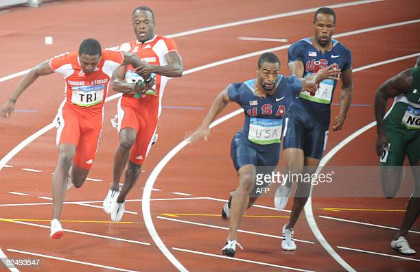 Darvis Patton of the US hands over the baton to fellow countryman Tyson Gay as they compete against Trinidad and Tobago's Richard Thompson and Aaron...