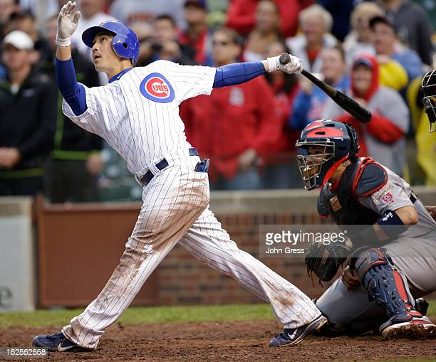 Darwin Barney of the Chicago Cubs hits a tworun home run as Yadier Molina of the St Louis Cardinals looks on in the ninth inning of their MLB game at...