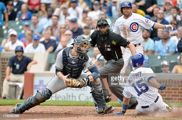 Darwin Barney of the Chicago Cubs scores past catcher Jonathan Lucroy of the Milwaukee Brewerson an RBI single hit by Carlos Villanueva during the...