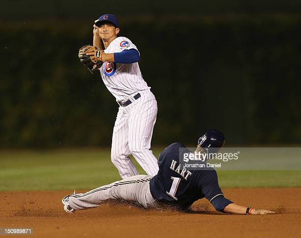 Darwin Barney of the Chicago Cubs tries to turn a double play as Corey Hart of the Milwaukee Brewers slides in at Wrigley Field on August 29 2012 in...