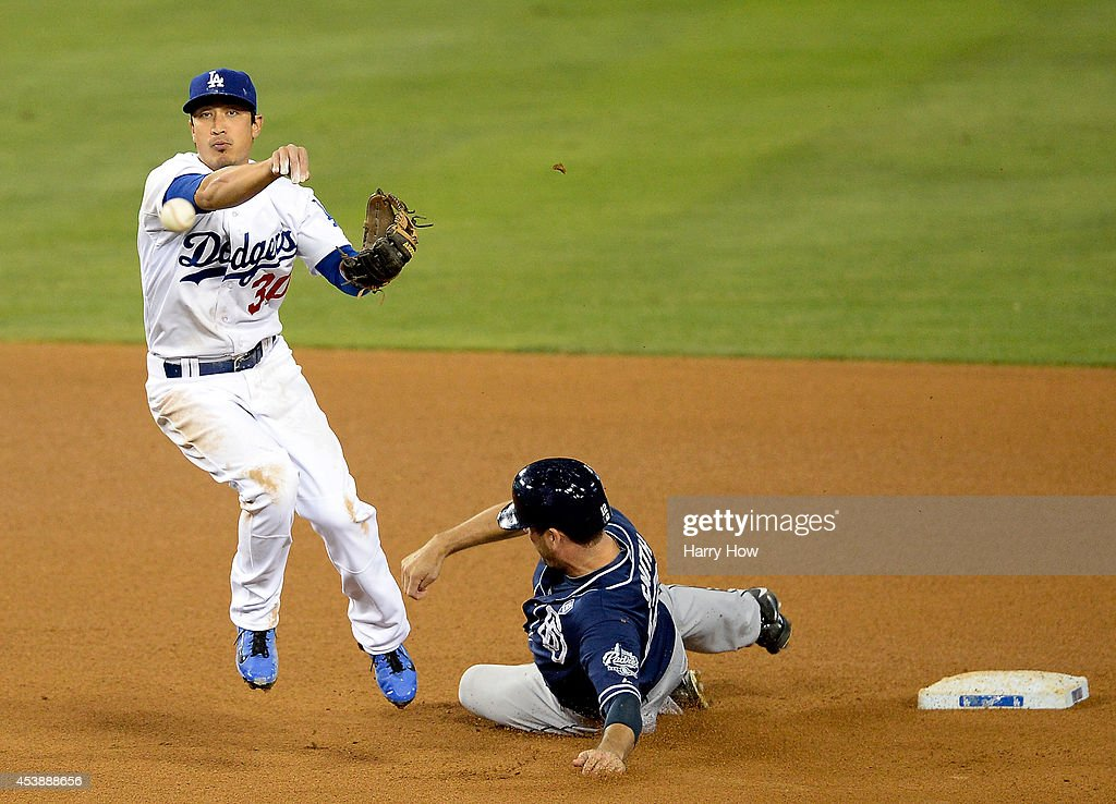 Darwin Barney #30 of the Los Angeles Dodgers turns a double play in front of Seth Smith #12 of the San Diego Padres during the fifth inning at Dodger Stadium on August 20, 2014 in Los Angeles, California.
