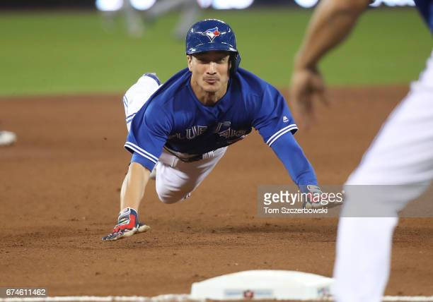 Darwin Barney of the Toronto Blue Jays advances safely from first base to third base on a single by Jose Bautista in the fifth inning during MLB game...