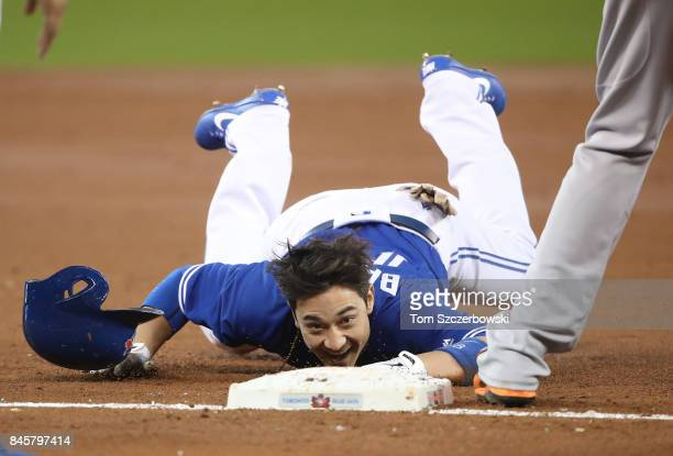 Darwin Barney of the Toronto Blue Jays crawls into third base after stumbling in the second inning during MLB game action against the Baltimore...