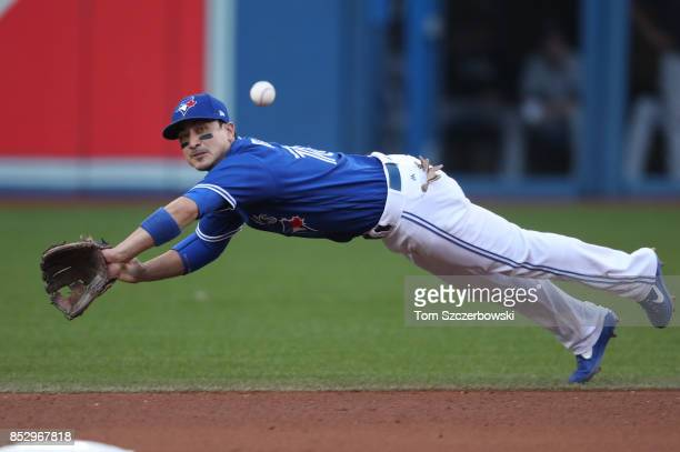 Darwin Barney of the Toronto Blue Jays dives but cannot snag a linedrive single by Jacoby Ellsbury of the New York Yankees in the seventh inning...
