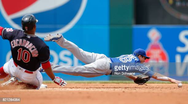 Darwin Barney of the Toronto Blue Jays dives for a ball on a throwing error by Josh Donaldson allowing Edwin Encarnacion of the Cleveland Indians to...