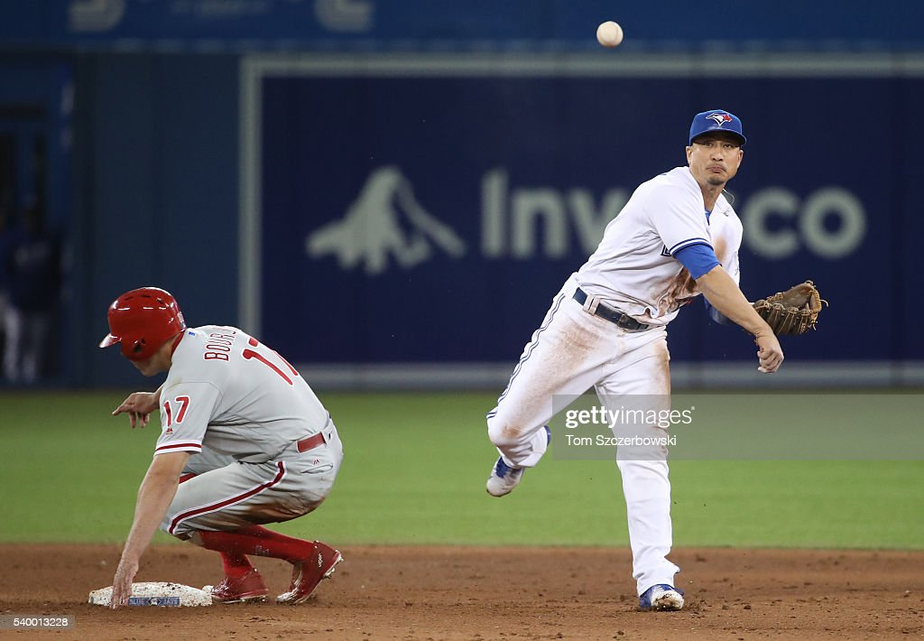 Darwin Barney #18 of the Toronto Blue Jays gets the force out on as Peter Bourjos #17 of the Philadelphia Phillies at second base but did not turn the double play at first base in the ninth inning during MLB game action on June 13, 2016 at Rogers Centre in Toronto, Ontario, Canada.