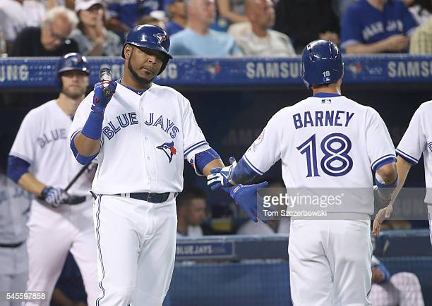 Darwin Barney of the Toronto Blue Jays is congratulated by Edwin Encarnacion after scoring a run in the fifth inning during MLB game action against...