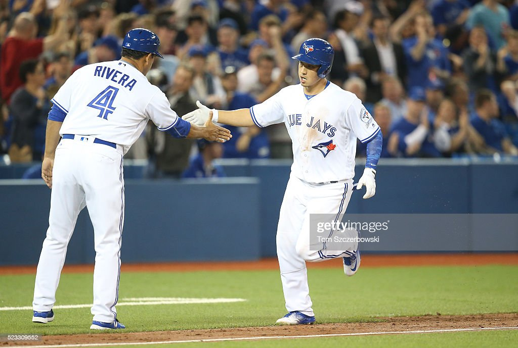 Darwin Barney #18 of the Toronto Blue Jays is congratulated by third base coach Luis Rivera #2 after hitting a solo home run in the third inning during MLB game action against the Oakland Athletics on April 22, 2016 at Rogers Centre in Toronto, Ontario, Canada.