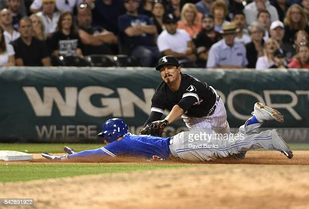 Darwin Barney of the Toronto Blue Jays is safe at third base as Tyler Saladino of the Chicago White Sox makes a tag during the ninth inning on June...