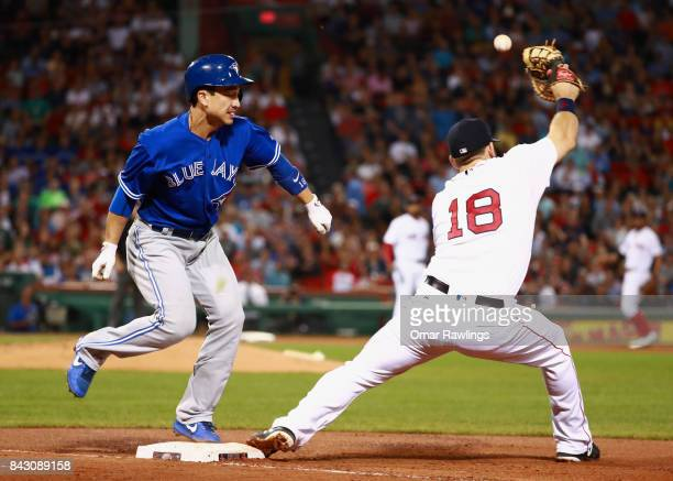 Darwin Barney of the Toronto Blue Jays safe at first base after a throwing error by short stop Xander Bogaerts of the Boston Red Sox as Mitch...