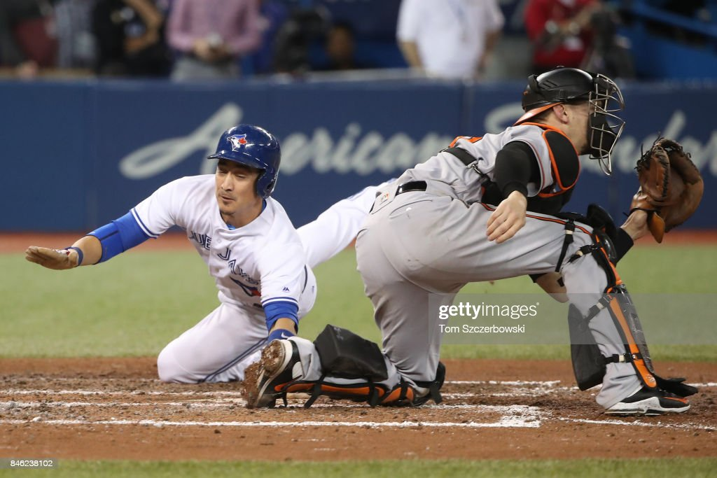 Darwin Barney #18 of the Toronto Blue Jays slides across home plate to score the game-winning run on an RBI single by Richard Urena #7 in the ninth inning during MLB game action against the Baltimore Orioles at Rogers Centre on September 12, 2017 in Toronto, Canada.