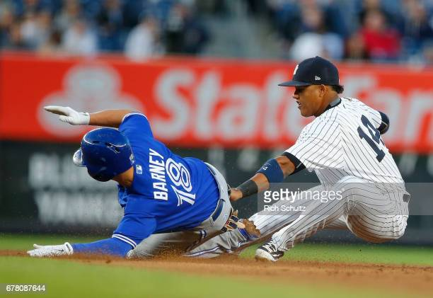 Darwin Barney of the Toronto Blue Jays slides safely into second base for a double before the tag of Starlin Castro of the New York Yankees in the...