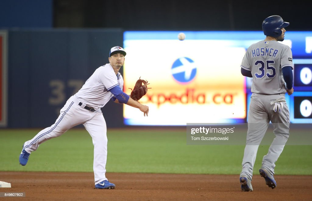 Darwin Barney #18 of the Toronto Blue Jays turns a double play in the fourth inning during MLB game action as Eric Hosmer #35 of the Kansas City Royals peels off the base line short of second base at Rogers Centre on September 19, 2017 in Toronto, Canada.