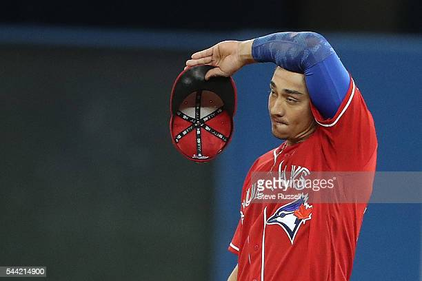 Darwin Barney wipes away sweat as the Toronto Blue Jays lose the Cleveland Indians 2-1 in 19 innings on Canada Day at the Rogers Centre in Toronto....