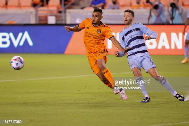 Darwin Ceren of Houston Dynamo chases the ball alongside Ilie Sanchez of Sporting Kansas City during the second half at BBVA Stadium on May 12, 2021...
