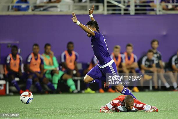 Darwin Ceren of Orlando City SC leaps over Teal Bunbury of the New England Revolution during an MLS soccer match between the New England Revolution...