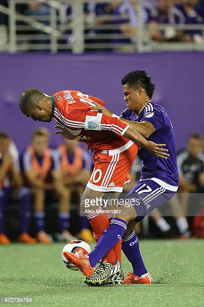 Darwin Ceren of Orlando City SC tackles Teal Bunbury of the New England Revolution during an MLS soccer match between the New England Revolution and...