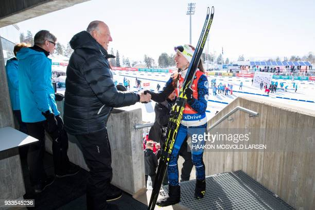 Darya Domracheva from Belarus is congratulated by King Harald V of Norway after winning the IBU Biathlon World Cup Women's 10 km Pursuit event in...