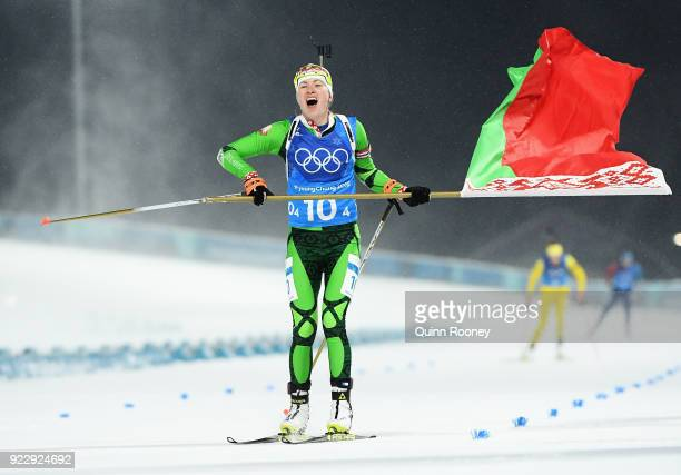 Darya Domracheva of Belarus celebrates with a flag as she approaches the finish line to win gold during the Women's 4x6km Relay on day 13 of the...