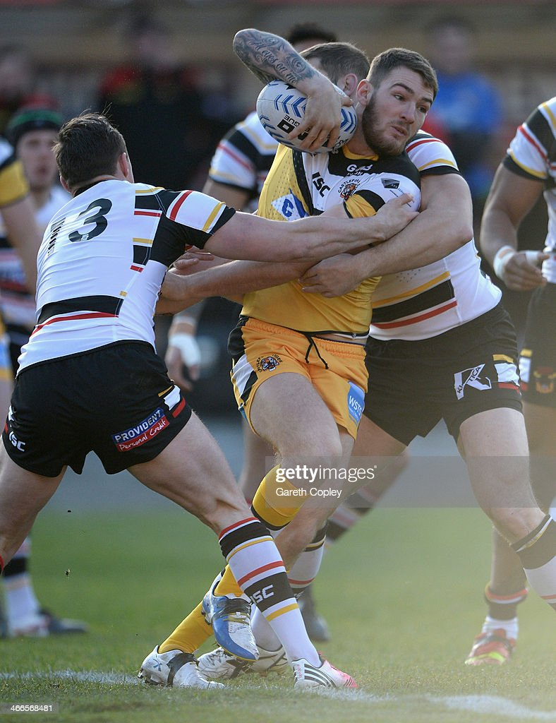 Daryl Clark of Castleford is tackled by James Donaldson of Bradford during the pre season friendly match between Bradford Bulls and Castleford Tigers at Odsal Stadium on February 2, 2014 in Bradford, England.