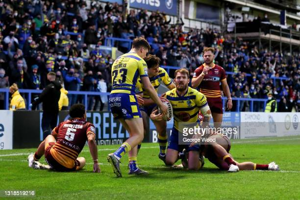Daryl Clark of Warrington Wolves celebrates with team mates after scoring their side's second try during the Betfred Super League match between...