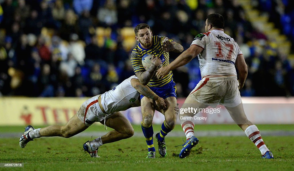 Daryl Clark of Warrington Wolves is tackled by Jack de Belin and George Rose of St George Illawarra Dragons during the World Club Series match between Warrington Wolves and St George Illawarra Dragons at The Halliwell Jones Stadium on February 20, 2015 in Warrington, England.