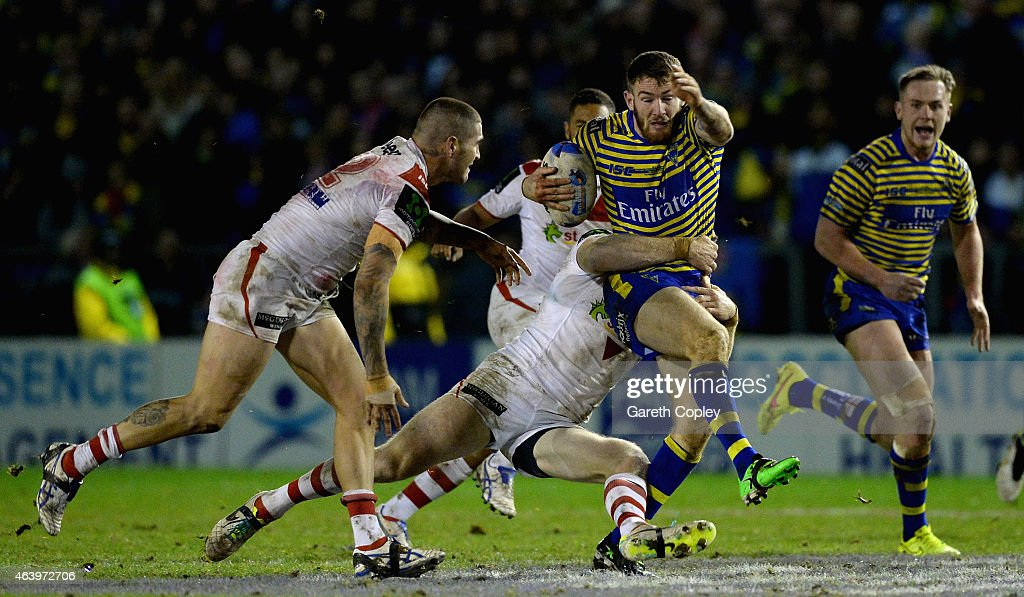 Daryl Clark of Warrington Wolves is tackled by Josh Dugan of St George Illawarra Dragons during the World Club Series match between Warrington Wolves and St George Illawarra Dragons at The Halliwell Jones Stadium on February 20, 2015 in Warrington, England.