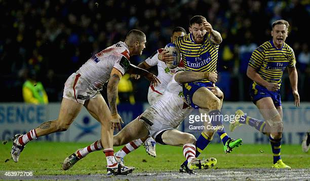 Daryl Clark of Warrington Wolves is tackled by Josh Dugan of St George Illawarra Dragons during the World Club Series match between Warrington Wolves...