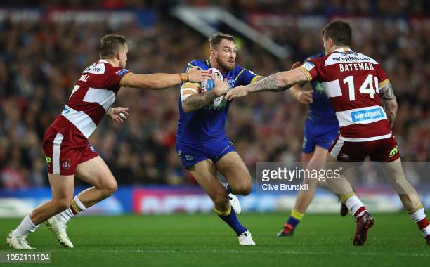 Daryl Clark of Warrington Wolves is tackled by Sam Powell and John Bateman of the Wigan Warriors during the BetFred Super League Grand Final between...
