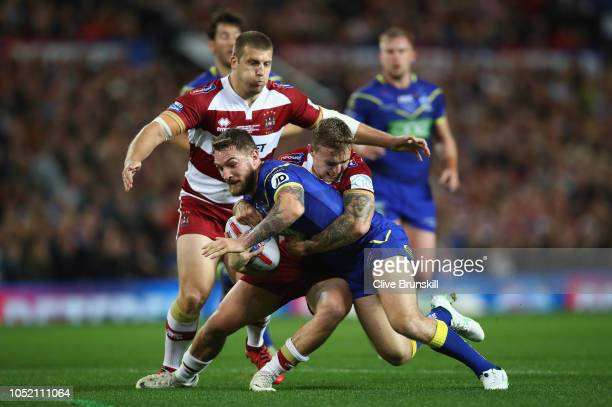 Daryl Clark of Warrington Wolves is tackled by Sam Powell of the Wigan Warriors during the BetFred Super League Grand Final between Warrington Wolves...