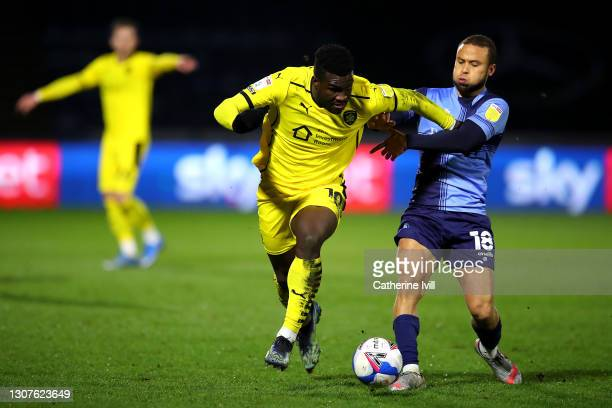 Daryl Dike of Barnsley FC is challenged by Curtis Thompson of Wycombe Wanderers during the Sky Bet Championship match between Wycombe Wanderers and...