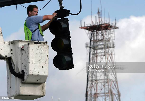 Daryl Jernigan puts up a new traffic signal the day after Hurricane Dennis passed through the area July 11 2005 in downtown Pensacola Florida Dennis...