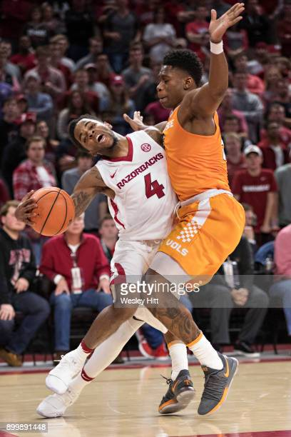 Daryl Macon of the Arkansas Razorbacks drives to the basket and is fouled by Admiral Schofield of the Tennessee Volunteers at Bud Walton Arena on...