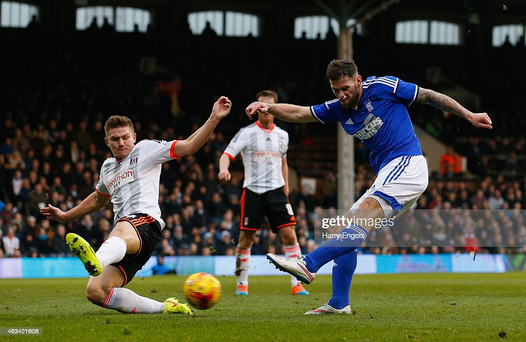 Daryl Murphy of Ipswich Town shoots at goal under pressure from Shaun Hutchinson of Fulham during the Sky Bet Championship match between Fulham and Ipswich Town at Craven Cottage on February 14, 2015 in London, England.
