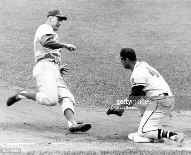 Daryl Spencer of the Los Angeles Dodgers is tagged out by third baseman Eddie Mathews of the Milwaukee Braves during an MLB game circa 1962 at County...