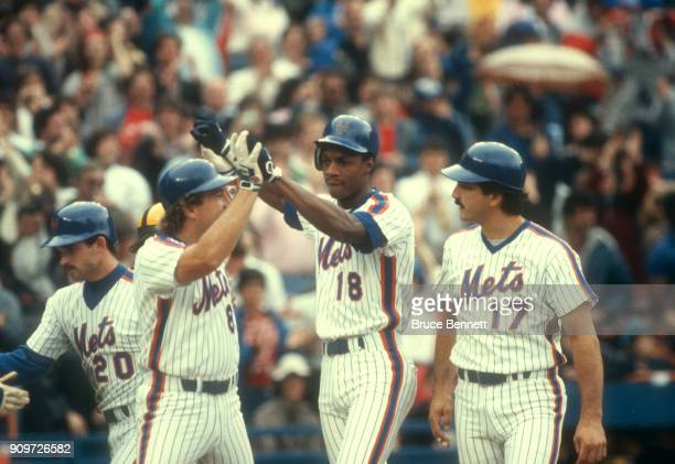 Daryl Strawberry of the New York Mets is congratulated by teammates Gary Carter and Keith Hernandez after hitting a homerun during an MLB game...