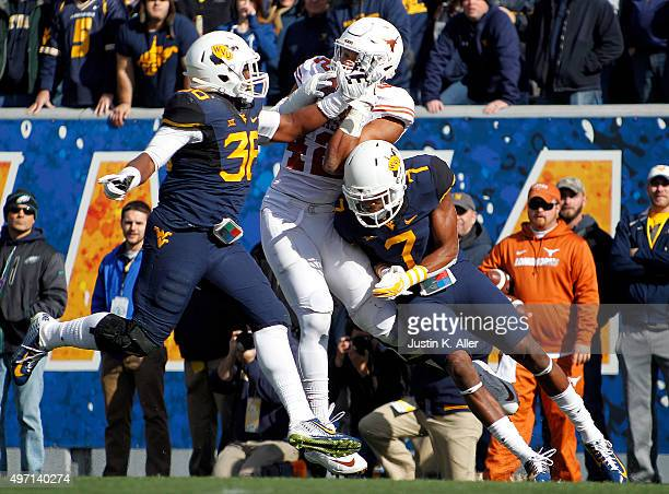 Daryl Worley and Shaq Petteway of the West Virginia Mountaineers knock the ball out of the hands of Caleb Bluiett of the Texas Longhorns in the firs...