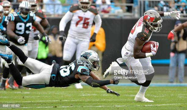 Daryl Worley of the Carolina Panthers dives to tackle Chris Godwin of the Tampa Bay Buccaneers during their game at Bank of America Stadium on...