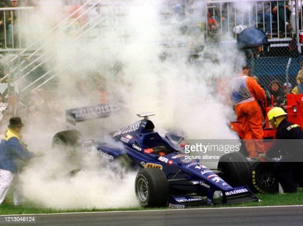Das Fahrzeug des italienische Prost-Peugeot-Pilot Jarno Trulli wird am 7.6.1998 beim Großen Preis von Kanada in Montreal durch Rettungskräfte...