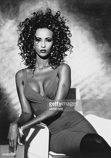 Das Fotomodell Iman sitzt in einem dekolletierten Kleid auf einem Sessel Aufgenommen um 1992