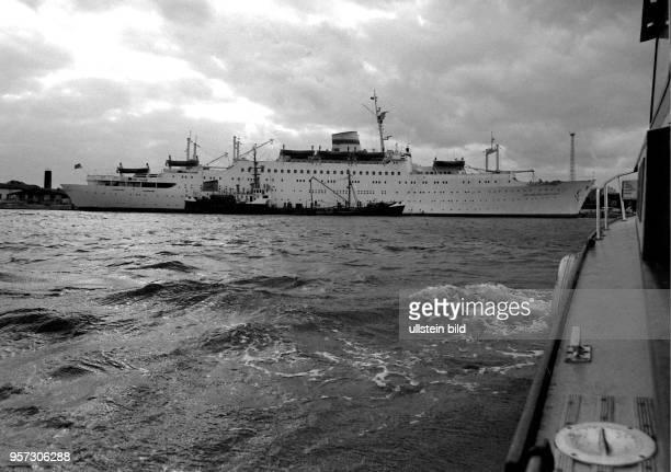 Das Lotsenboot Wels im Anmarsch zum Passagierschiff Völkerfreundschaft am Warnemünder Passagierkai aufgenommen in den 1980er Jahren in Rostock Bei...