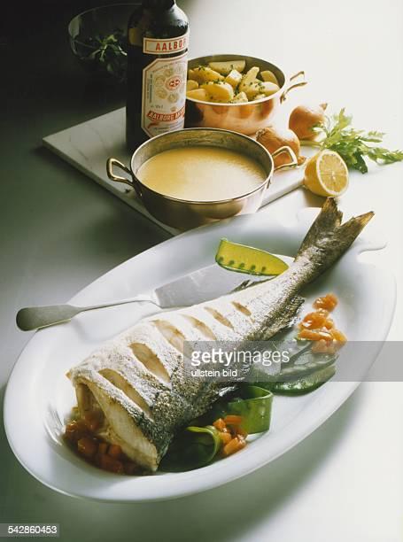 Das mehrmals eingeschnittene Schwanzstück eines gebackenen Schellfisches zusammen mit Gemüse auf einer Servierplatte. Dahinter auf einer Marmorplatte...