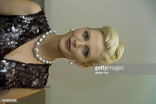 Das Model Nadja Auermann mit hochgesteckten Haaren und einer Perlenkette