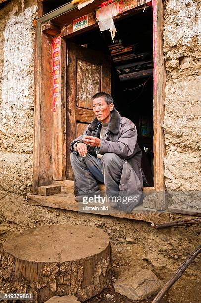 das Naturreservat Meili Xue Shan mit dem Dorf Yubeng mit einem Mann vor der Haustuere