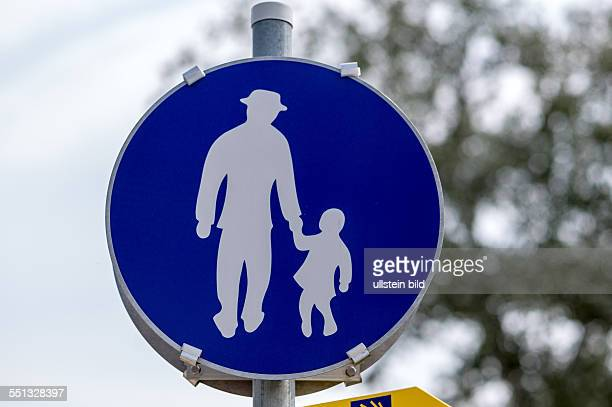 Das Schild Gehweg in Österreich mit Vater und Tochter