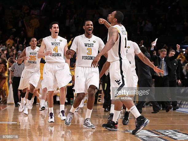 Da'Sean Butler of the West Virginia Mountaineers celebrates with teammates Wellington Smith Jonnie West and Devin Ebanks after making a game winning...